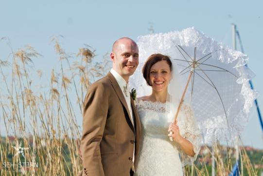 Brautpaar mit Sonnenschirm fotografiert von Hochzeitsfotograf Marion Hogl aus München